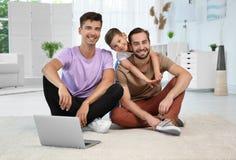 Pareja gay masculina con el hijo adoptivo que se sienta en piso en casa Imágenes de archivo libres de regalías