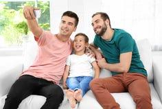 Pareja gay masculina con el hijo adoptivo que toma el selfie Imagenes de archivo