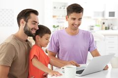 Pareja gay masculina feliz con el hijo adoptivo en casa Foto de archivo libre de regalías
