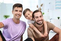 Pareja gay masculina feliz con el hijo adoptivo en casa Fotografía de archivo
