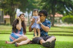 Pareja japonesa asiática cariñosa feliz joven de los padres que goza junto del bebé dulce de la hija que asiste en hierba en el p fotografía de archivo