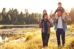 Pareja masculina gay con los niños que caminan por el lago Fotos de archivo