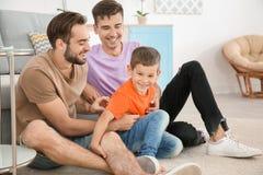 Pareja masculina homosexual con el hijo adoptivo en casa Fotos de archivo