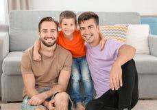 Pareja masculina homosexual con el hijo adoptivo en casa Imágenes de archivo libres de regalías