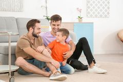 Pareja masculina homosexual con el hijo adoptivo en casa Fotografía de archivo