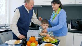 Pareja mayor del pensionista que abraza al niño en el tiempo del almuerzo en cocina cerca de la tabla con la comida deliciosa almacen de metraje de vídeo