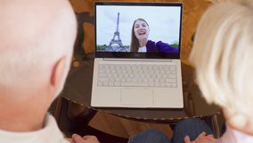 Pareja mayor en casa que tiene charla video con la hija del estudiante de París, torre Eiffel en fondo almacen de metraje de vídeo