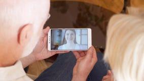 Pareja mayor en casa que tiene charla video vía llamada del app del mensajero en móvil con su hija en el extranjero metrajes