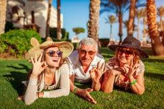 Pareja mayor que miente en hierba con la hija adulta por el hotel Gente feliz que disfruta de vacaciones Valores familiares imagen de archivo libre de regalías