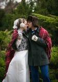 Pareja nuevamente casada feliz que se besa en el bosque del invierno Imagenes de archivo