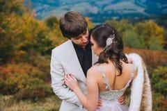 Pareja nuevamente casada que presenta en las montañas Foto de archivo