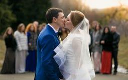 Pareja nuevamente casada que se besa delante de huéspedes felices en el parque Imagen de archivo