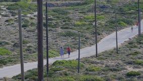 Pareja que camina con los niños corrientes en el camino rural almacen de metraje de vídeo