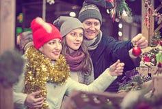 Pareja satisfecha de la familia con la hija adolescente que elige la Navidad de Imagen de archivo