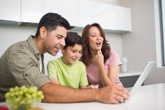 Pareja sonriente con el hijo que usa el ordenador portátil Imagen de archivo libre de regalías