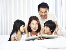 Pareja y libro de lectura asiáticos de dos niños junto en cama fotografía de archivo