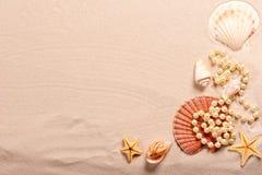 Parelparels en zeeschelpen in zand Stock Foto's