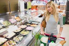 Parement de la vue de la femme blonde regardant des produits sur le buffet cuisiné de plat image stock