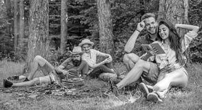 Paren of families die het grote tijd ontspannen hebben dichtbij kampvuur De paren brengen in openlucht tijd op zonnige dag door P stock fotografie