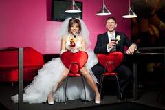paren i sammanträdet för bröllopdag i de röda stolarna med hjärtan i coctailen för billiardrum och drink royaltyfri foto