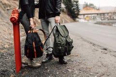 Paren reser Pojke och flicka med ryggsäcklopp Paret är på vägen Artikel med ensamrättryggsäckar i hans Royaltyfria Bilder