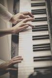 Paren, speelmuziek met de piano gelijktijdig royalty-vrije stock foto's