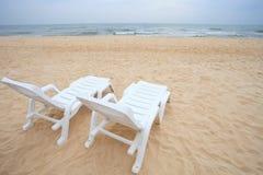 Paren van ligstoelen op zandstrand Stock Fotografie