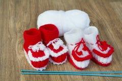 Paren van met de hand gemaakte witte en rode gebreide pantoffels en garenbal Royalty-vrije Stock Afbeelding