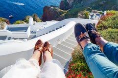 Parenbenen die de zomer van dag genieten bij Santorini-eiland Stock Foto