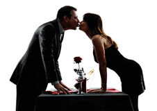 Parenminnaars die dinersilhouetten kussen Stock Afbeeldingen