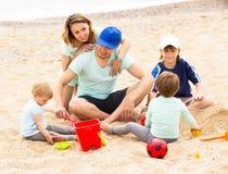 Parens sonrientes con tres niños en la playa arenosa Imagen de archivo libre de regalías