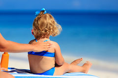 Parent applying sunblock cream on daughter Royalty Free Stock Images