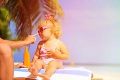 Parent applying sunblock cream on daughter Stock Image