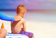 Parent applying sunblock cream on son shoulder Stock Images