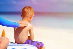 Parent applying sunblock cream on son shoulder Stock Images