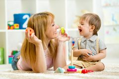 Parent and baby boy playing together at home Stock Photos
