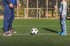 Parent and boy standing near ball. Father is teaching son to play football. They are standing on green field. Close-up of their legs Royalty Free Stock Photography