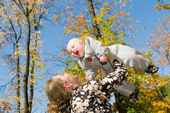 Parent care. Little child embraces mother and looks out at her shoulder Royalty Free Stock Images