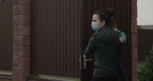 Parent with Child Closing Door wearing Face Masks a Concept of self-isolation and social distancing because of Pandemia of Coronav