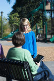 Parent Child Discussion. A mother listens to an explanation by her daughter at a community playground stock image