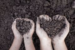 Parent and child hand holding soil in heart shape for planting. Together Royalty Free Stock Image