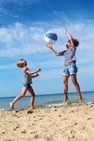 Parent and child play a ball at coast on a summer day Stock Photography