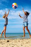 Parent and child play a ball at coast on a sunny summer day Stock Image