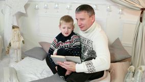 Parent and a child read a story, father and his little son reading a book together, family reading at home, a good stock video footage