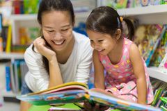 Parent and child reading books together in the library stock photo