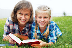 Parent and child reading books together in the park Stock Photo