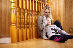 Parent with child sitting on the floor near the wooden railing Stock Photos