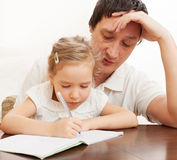 Parent with child writing. Father helping daughter doing homework. Parent with child writing Royalty Free Stock Photo