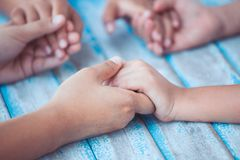 Parent and children holding hands and praying together. On blue wooden table Stock Photo