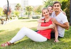 Parent con el muchacho en la edad adolescente que se sienta en hierba verde en parque Foto de archivo